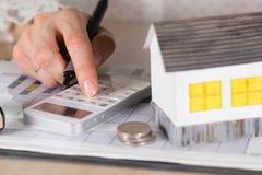 La giovane donna effettua alcuni calcoli Piccola casa di carta, monete, c fotografie stock libere da diritti