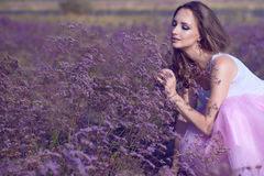 La giovane donna elegante con artistico compongono ed i fiori viola odoranti dei capelli lunghi di volo con gli occhi chiusi fotografia stock