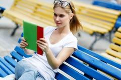 La giovane donna esamina il computer della compressa che si siede sul banco Fotografia Stock Libera da Diritti