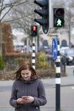 La giovane donna esamina il suo cellulare e non presta attenzione a Fotografie Stock Libere da Diritti