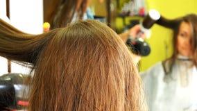 La giovane donna la esamina nello specchio in un salone di bellezza, sedentesi in una sedia stock footage
