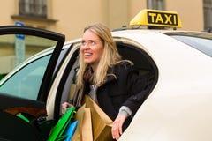 La giovane donna esce del taxi Fotografie Stock Libere da Diritti