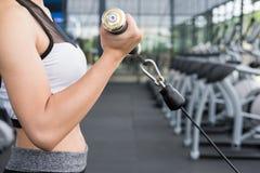 La giovane donna esegue l'esercizio con la macchina nel centro di forma fisica fem fotografie stock libere da diritti
