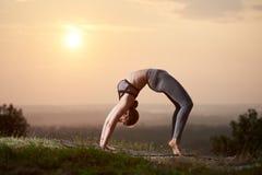 La giovane donna esile attraente che fa l'yoga si esercita all'aperto sul fondo dello spazio della copia di bello cielo immagine stock