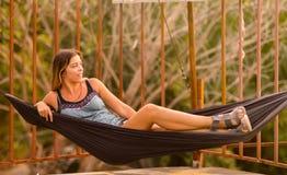 La giovane donna esile nel tramonto esotico tropicale dell'amaca si accende immagine stock