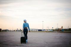 La giovane donna esile vestita in blu ha controllato la camicia, cappuccio ed i jeans, partiranno all'alba il giorno di estate su Fotografia Stock