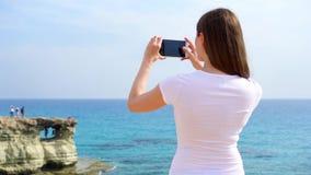 La giovane donna fa la foto sul cellulare contro il mar Mediterraneo blu al rallentatore Vista da dietro video d archivio