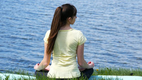La giovane donna fa gli esercizi che le curvature si dirigono avanti e indietro Immagine Stock