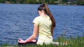 La giovane donna fa gli esercizi che le curvature si dirigono avanti e indietro Fotografia Stock