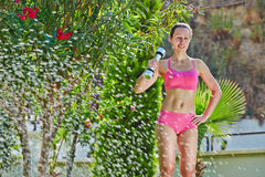 La giovane donna fa gli esercizi della testa di legno nel giardino di mattina Fotografia Stock Libera da Diritti