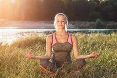 La giovane donna fa gli esercizi di yoga Fotografia Stock