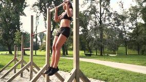 La giovane donna fa i vari esercizi di peso corporeo alla barra orizzontale archivi video