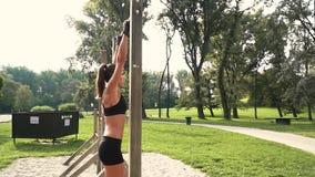 La giovane donna fa i vari esercizi di peso corporeo alla barra orizzontale video d archivio