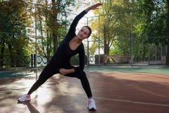 La giovane donna fa l'allungamento degli esercizi durante l'attività di formazione di sport Immagini Stock Libere da Diritti