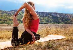 La giovane donna fa l'esercizio flessibile di yoga fotografie stock libere da diritti