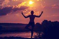 La giovane donna fa l'yoga o la forma fisica al tramonto Siluetta sul sole del fondo immagini stock