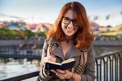 La giovane donna fa le note in suo diario La studentessa annota le nuove informazioni e fa un compito di scrittura Fotografie Stock Libere da Diritti