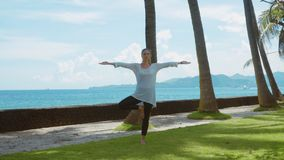 La giovane donna fa la pratica di yoga, rilassantesi ed allungante su sulla spiaggia vicino all'oceano calmo sull'isola Bali con  video d archivio