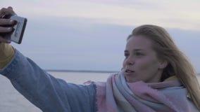 La giovane donna fa un selfie sulla spiaggia di autunno al telefono video d archivio