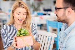 La giovane donna felice è sorpresa dopo la ricezione del regalo di anniversario o di compleanno dal suo ragazzo immagini stock libere da diritti