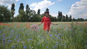 La giovane donna felice allegra in vestito rosso passa il campo di fioritura dei papaveri Video del hd del movimento lento stock footage
