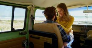 La giovane donna felice che si siede sopra equipaggia il rivestimento in furgone un giorno soleggiato 4k video d archivio