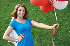 La giovane donna felice con il lattice variopinto balloons, all'aperto immagine stock