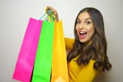 La giovane donna felice con il negozio variopinto insacca in pieno dei vestiti in sua mano su fondo grigio Fotografie Stock