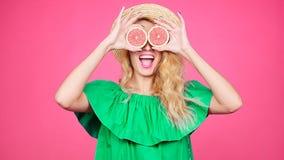 La giovane donna felice con la metà due del pompelmo succoso invece osserva stock footage