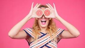 La giovane donna felice con la metà due del pompelmo succoso invece osserva video d archivio