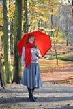 La giovane donna felice costa con un ombrello rosso nel parco di autunno Fotografie Stock