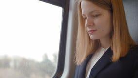 La giovane donna felice di affari sta lavorando al computer portatile e sta sorridendo mentre andava in treno archivi video