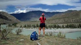 La giovane donna felice di torist sta stando al bordo della montagna e sta prendendo a foto il paesaggio scenico Vista posteriore stock footage