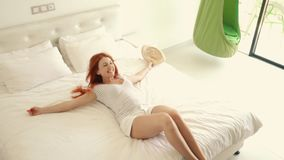 La giovane donna felice flops sul letto in suo nuovo appartamento video d archivio