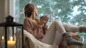 La giovane donna felice gode di della tazza di caffè caldo che si siede a casa dalla grande finestra con il fondo dell'albero del archivi video
