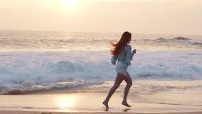 La giovane donna felice gode di di rilassarsi sull'oceano, movimento lento stock footage