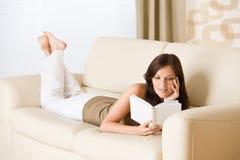 La giovane donna felice ha letto il libro sul sofà Immagine Stock