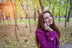 La giovane donna felice parla su uno smartphone nel parco di autunno fotografia stock libera da diritti