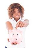La giovane donna felice risparmia i soldi in porcellino salvadanaio Fotografie Stock Libere da Diritti