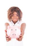 La giovane donna felice risparmia i soldi in porcellino salvadanaio Immagine Stock Libera da Diritti