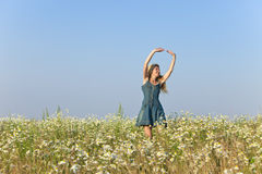 La giovane donna felice salta nel campo dei camomiles Immagine Stock