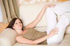 La giovane donna felice si distende la menzogne giù sul sofà immagini stock libere da diritti