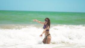 La giovane donna felice si imbatte nel mare con il lotto di spruzza e salto sopra l'onda di rottura video d archivio