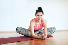 La giovane donna felice si rilassa facendo l'allungamento prima dell'esercizio Fotografie Stock