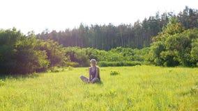 La giovane donna felice si siede su un prato inglese verde in un campo scenico su un fondo del tramonto video d archivio