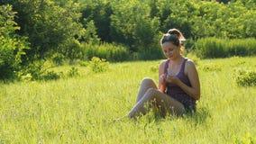 La giovane donna felice si siede su un prato inglese verde in un campo scenico su un fondo del tramonto archivi video