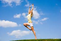 La giovane donna felice sta ballando in un campo Fotografie Stock