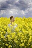 La giovane donna felice sta camminando nel giacimento del canola Fotografie Stock