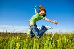 La giovane donna felice sta saltando in un campo Fotografie Stock Libere da Diritti