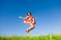 La giovane donna felice sta saltando in un campo Fotografia Stock Libera da Diritti